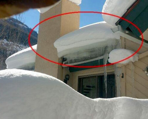 How not to take care of a home. Snow must be moved from time to time as needed. This large block of ice is crushing the wall below it. The door would not operate under it, the wall was bowed and the window one story down was being damaged as well.